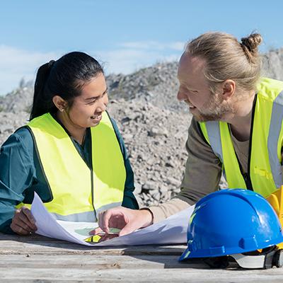 Två personer som kollar på en ritning och diskuterar ett byggprojekt.
